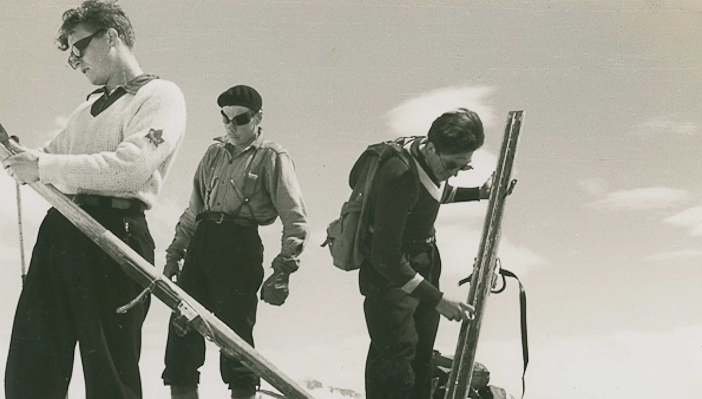 Waxing skis and displaying the height of inter-war era ski fashion.