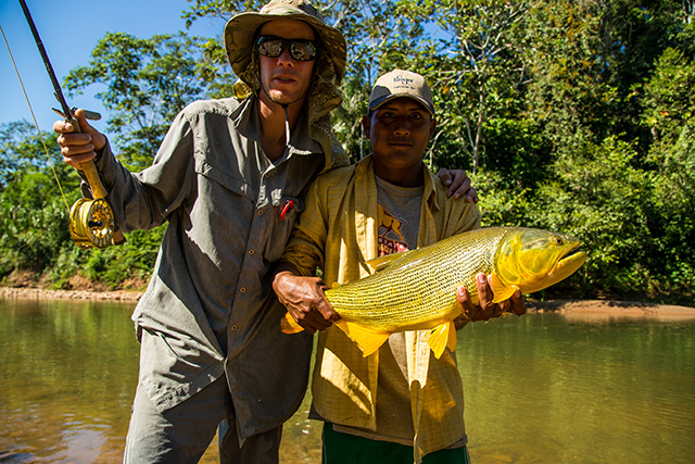 """""""A classic grip-and-grin shot. Patricio, with a mouth full of coca leaves, hoists up a nice dorado that he helped Neil bring in. These fish are pissed off when you try to land them, so having a buddy nearby is always helpful."""""""