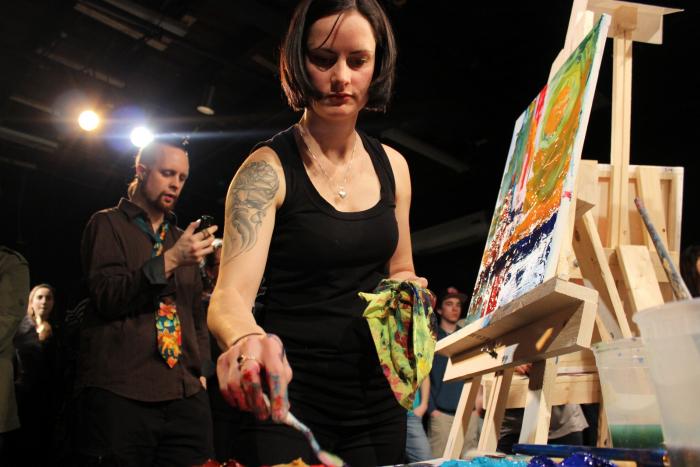 Grace Simms paints her way into battle. Photo by Dorian Geiger. Courtesy artbattle.ca