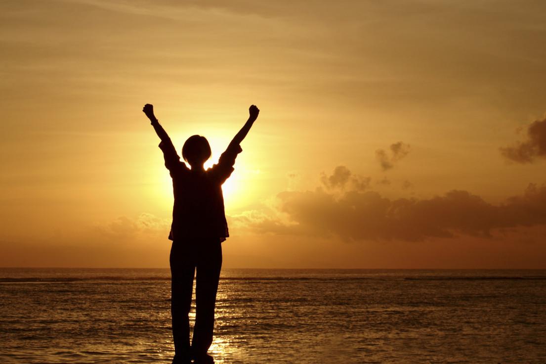 Woman raising her hands at sunrise