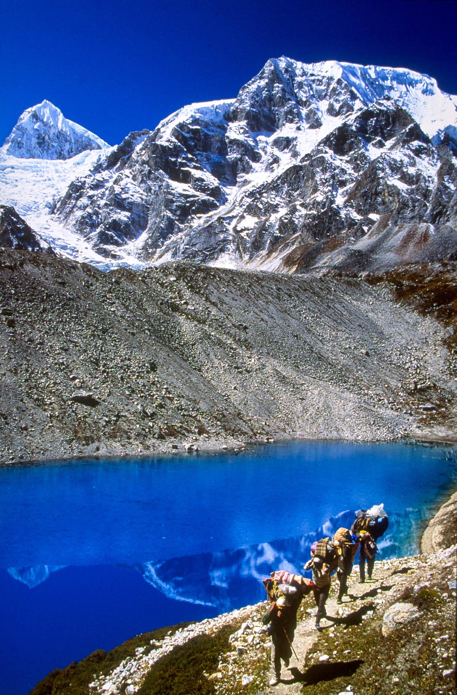 Porters walk along lakeside trail, Pang Phuchi mountain behind, east side of Larkya La (5135m), Manaslu area. Nepal. 1996.