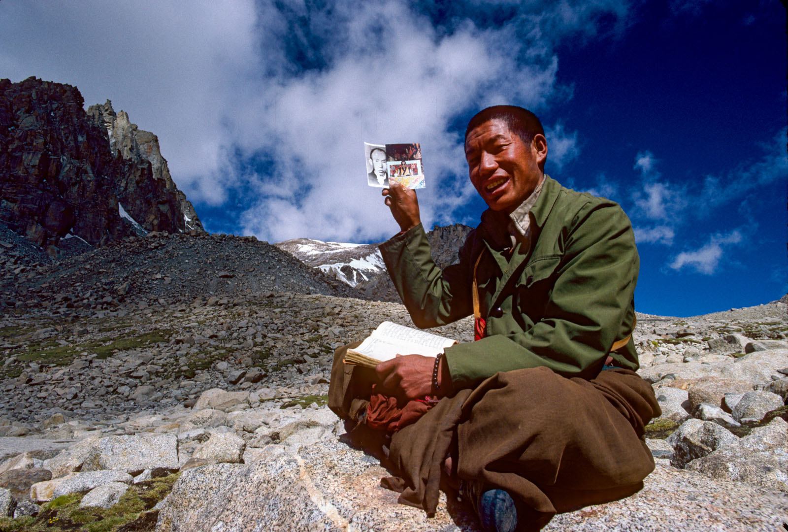 Tibetan monk on long one day kora (circuit) of holy Mt Kailash risks displaying a photo of the Dalai Lama which could land him in a Chinese prison if caught with it. Tibet. 1987