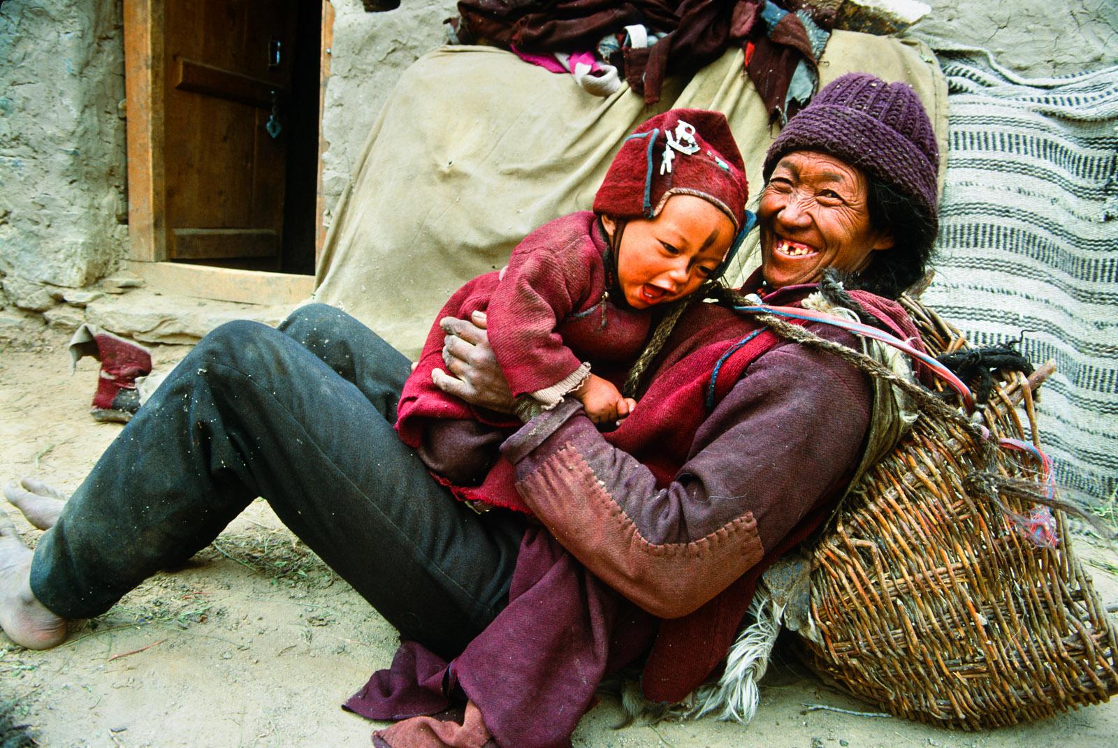 Ladakhi grandmother plays with child in Ating, district of Zanskar, Ladakh region. India .1993.