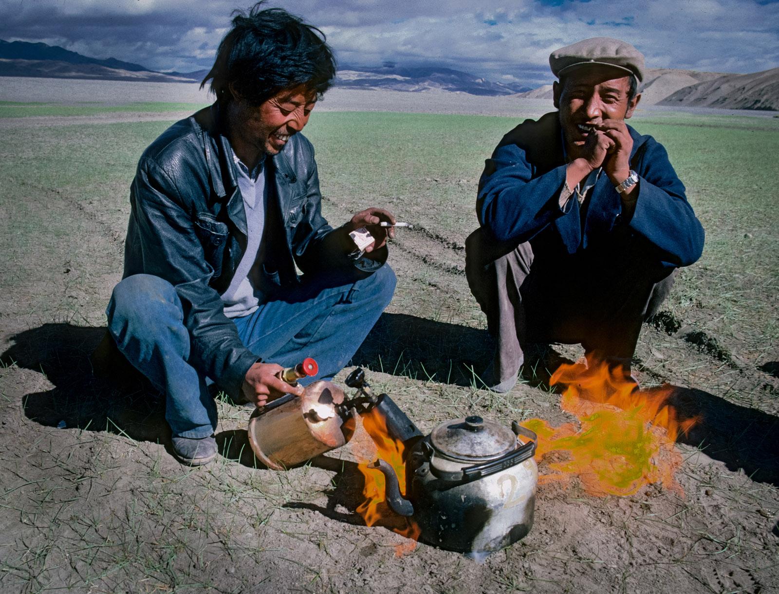 Gyatso, our Tibetan truck driver, brews up a pot of yak butter tea with his tiger torch. Changtang Plateau, Tibet. 1987