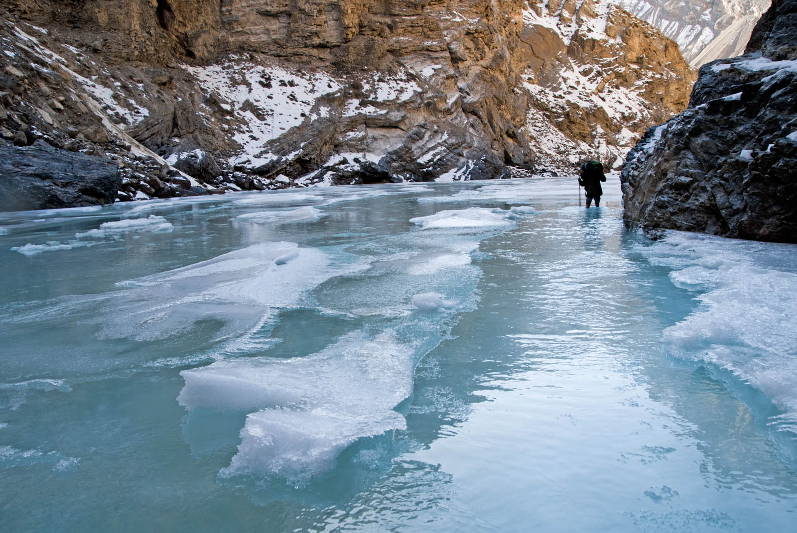 A porter ferrying a load in the Zanskar river in winter. Warm weather had forced water over the normally frozen layer of ice.