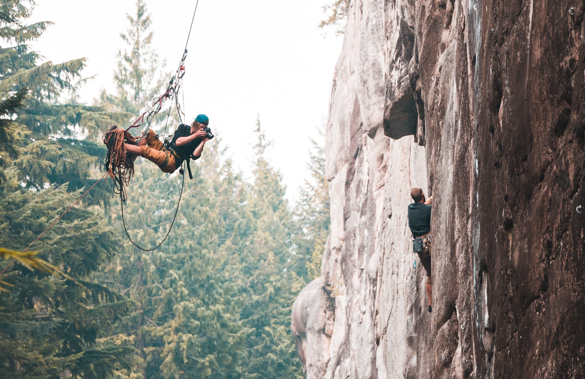 Photographer dangling from cliff wall taking photos of rock climber.