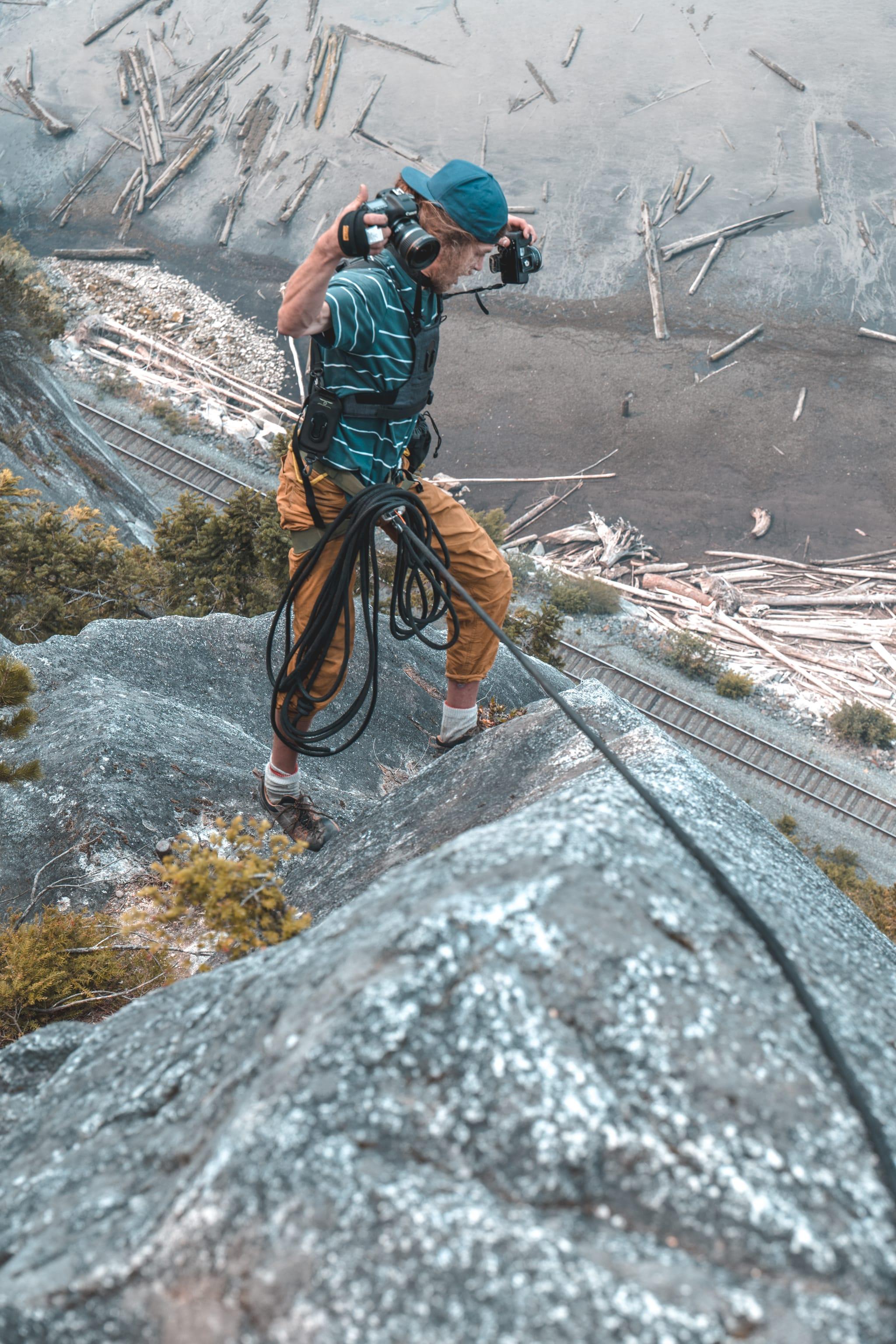 Photographer hanging on wall shooting a rock climber