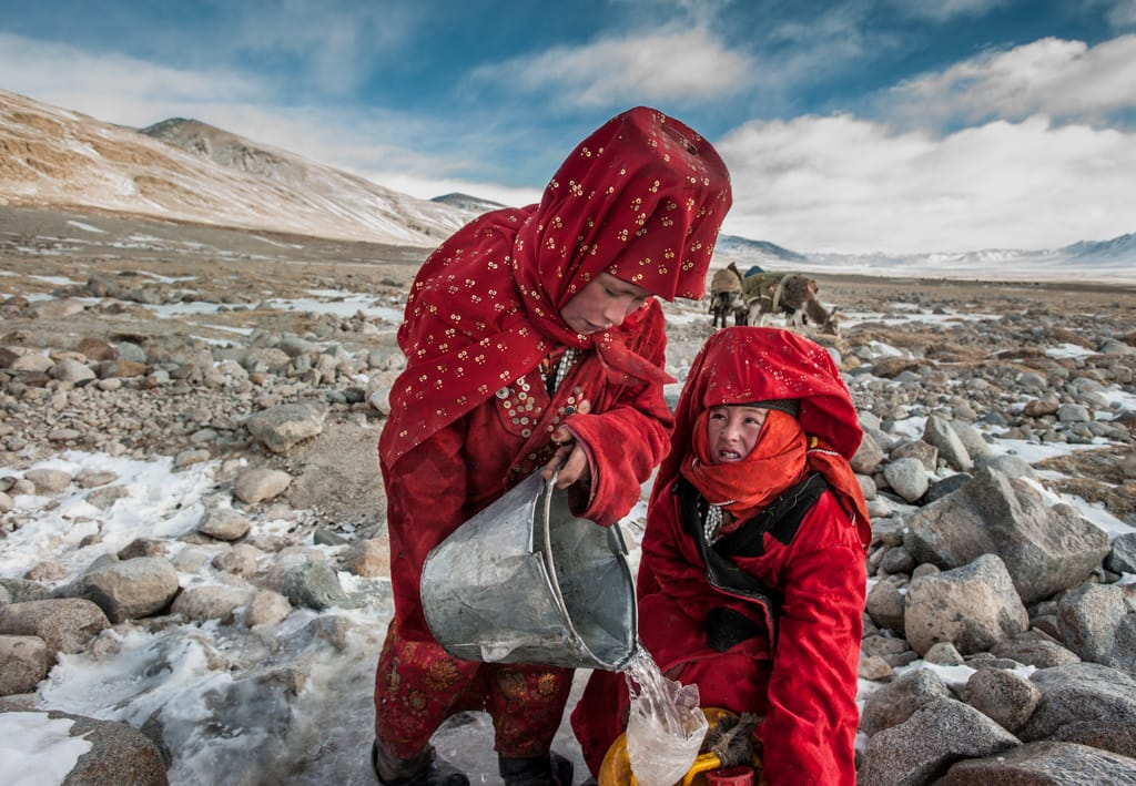 Kyrgyz girls in traditional red robes gathering water on frozen creek