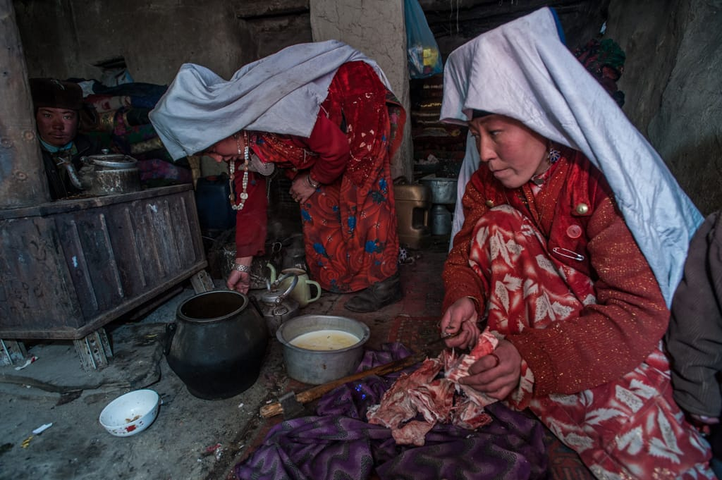 Kyrgyz women prepare a meal of yak meat and bones in a mud hut