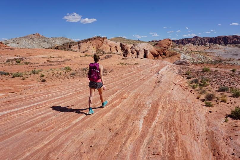 Corry Bondini hiking along slickrock in Fire State Park in Utah