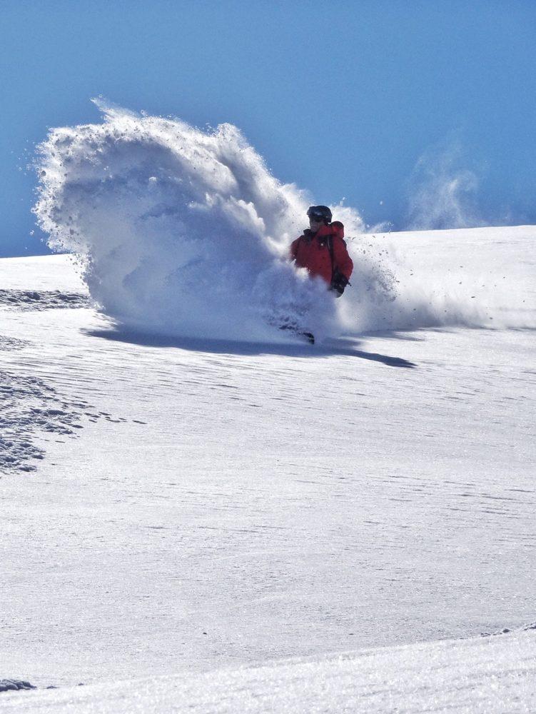 Snowboarder slashing a big powder turn.