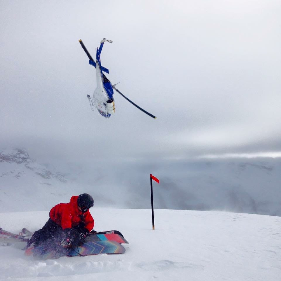 Heli guide covering the skis & boards while a heli buzzes away.