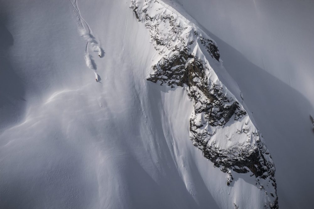 two heli skiers ripping an open slope of powder