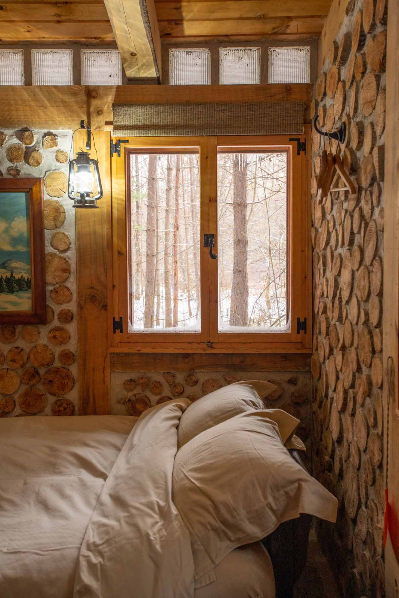 The-Cordwood-Cabin-An-Accessible-Retreat-from-the-21st-Century-bed-and-window-photo-by-Kristin-Schnelten